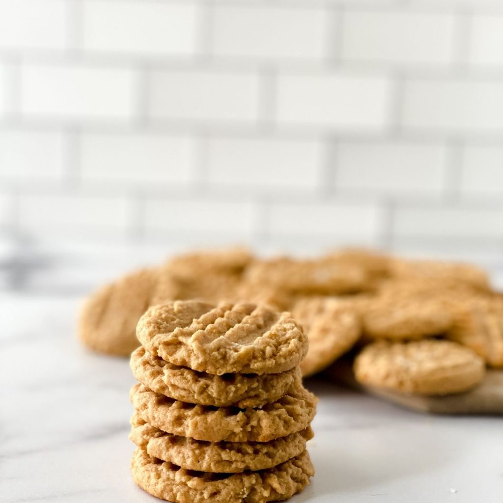 classic peanut butter cookies stacked on a counter with more cookies in the background
